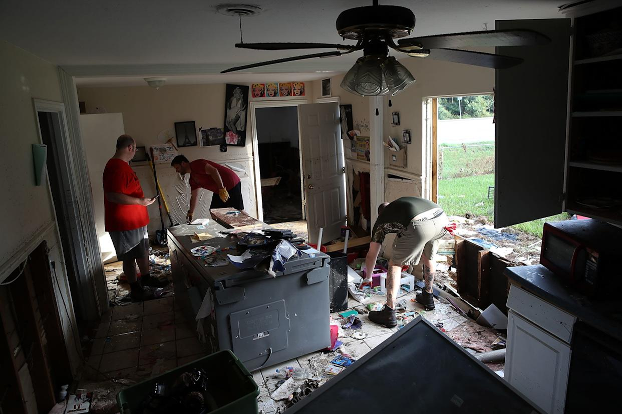 Bryan Parson (left), Chris Gaspard (center) and Derek Pelt (right) remove ruined items from Parson's home.