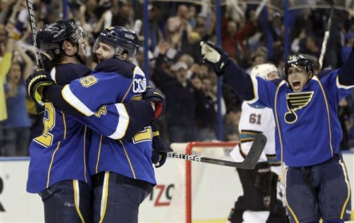 St. Louis Blues' David Backes, left, is congratulated by Carlo Colaiacovo, center, and David Perron, right, after scoring during the second period in Game 2 of an NHL Stanley Cup first-round hockey playoff series against the San Jose Sharks Saturday, April 14, 2012, in St. Louis. (AP Photo/Jeff Roberson)