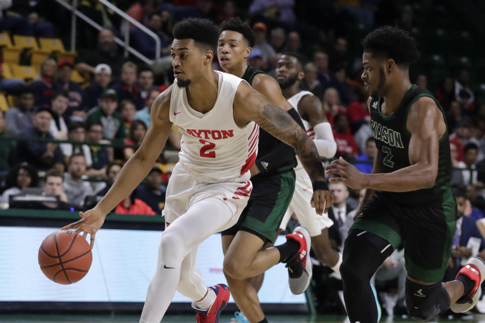 Dayton's Ibi Watson (2) moves the ball as George Mason's Xavier Johnson (2) defends during the first half of an NCAA college basketball game Tuesday, Feb. 25, 2020, in Fairfax, Va.(AP Photo/Luis M. Alvarez)