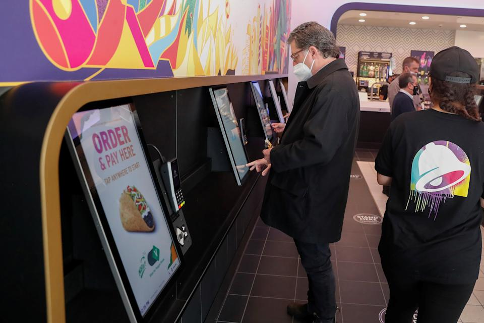 A customer orders at a Taco Bell digital kiosk inside the first digital-only U.S. cantina location at Times Square in New York City, U.S., April 14, 2021. REUTERS/Shannon Stapleton