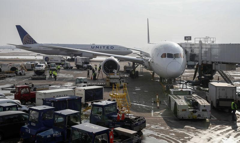 FILE PHOTO: A United Airlines Boeing 777 taxis past an Air New Zealand Boeing 787 plane at a gate at O'Hare International Airport in Chicago