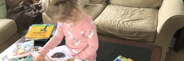 A young girl is reading book and sitting on the floor.