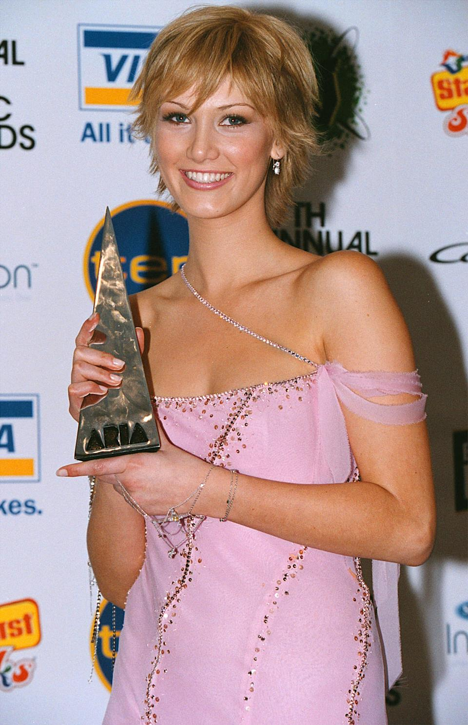Delta Goodrem poses in a pink dress and a short hairdo with her ARIA Award on the red carpet in October 2003, months after her cancer diagnosis