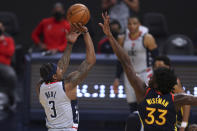 Washington Wizards forward Bradley Beal, left, shoots against Golden State Warriors center James Wiseman during the first half of an NBA basketball game in San Francisco, Friday, April 9, 2021. (AP Photo/Jed Jacobsohn)