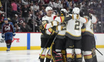 Vegas Golden Knights defenseman Nick Holden, goaltender Marc-Andre Fleury, defenseman Zach Whitecloud and right wing Reilly Smith celebrate with teammates after the Golden Knights scored in overtime of Game 5 of an NHL hockey Stanley Cup second-round playoff series, as Colorado Avalanche center Nathan MacKinnon, back, reacts Tuesday, June 8, 2021, in Denver. The Golden Knights won 3-2. (AP Photo/David Zalubowski)
