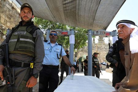 Israeli police officers stand guard next to newly installed metal detectors as a Palestinian man stands nearby at the entrance to the compound known to Muslims as Noble Sanctuary and to Jews as Temple Mount, in Jerusalem's Old City July 16, 2017. REUTERS/Ammar Awad