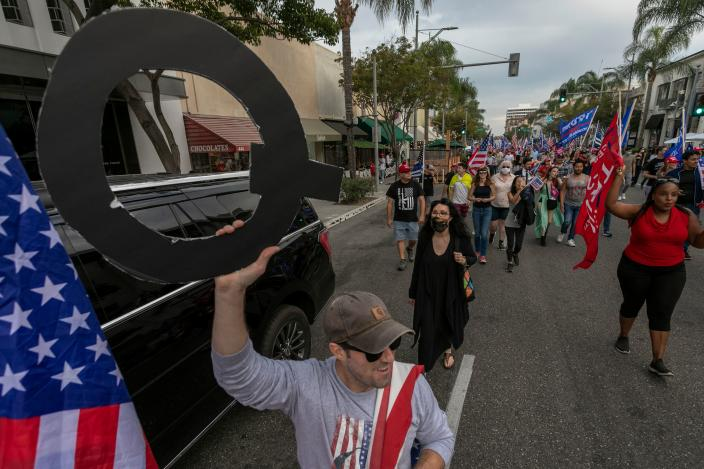 A man carries QAnon conspiracy theory signage as US President Donald Trump supporters rally on Halloween during the last weekend before the presidential election day in Beverly Hills, California, on October 31, 2020. (David McNew/AFP via Getty Images)