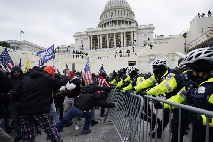 FILE - In this Jan. 6, 2021, file photo, Trump supporters try to break through a police barrier at the Capitol in Washington. A Chicago police officer has been charged with breaching the U.S. Capitol and entering a senator's office during the Jan. 6 insurrection. Karol Chwiesiuk, was arrested Friday, June 11 and faces five misdemeanor counts, including entering a restricted building, disrupting government business, and disorderly conduct on Capitol grounds with intent to impede congressional proceeding. (AP Photo/Julio Cortez, File)
