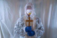 Father Stephan, a Ukrainian Greek Catholic Church priest, wearing a special suit to protect himself against coronavirus, stands, after visiting patients with COVID-19 at an intensive care unit of the emergency hospital in Lviv, Western Ukraine, Saturday, Jan. 9, 2021. Ukraine imposed a wide-ranging lockdown which began Friday, closing schools and entertainment venues and restaurant table service through Jan. 25. (AP Photo/Evgeniy Maloletka)