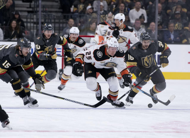 Vegas Golden Knights defenseman Jon Merrill (15) and right wing Tomas Hyka (38) battle for the puck against Anaheim Ducks right wing Ondrej Kase (25) during the first period of an NHL hockey game Wednesday, Nov. 14, 2018, in Las Vegas. (AP Photo/Eric Jamison)