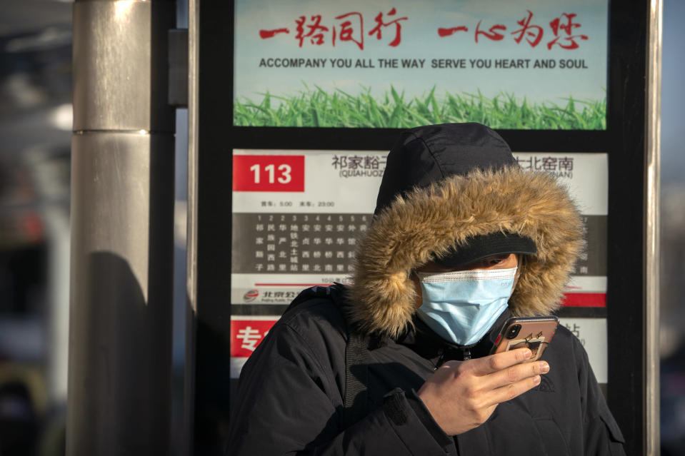 A woman wearing a face mask to protect against the spread of the coronavirus waits at a bus stop during the morning rush hour in Beijing, Wednesday, Dec. 30, 2020. Beijing has urged residents not to leave the city during the Lunar New Year holiday in February, implementing new restrictions and mass testings after several coronavirus infections last week. (AP Photo/Mark Schiefelbein)