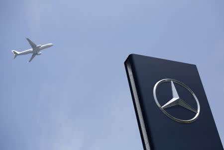 FILE PHOTO: A plane flies above as a Mercedes-Benz logo is seen outside its Shanghai office, August 5, 2014. REUTERS/Aly Song