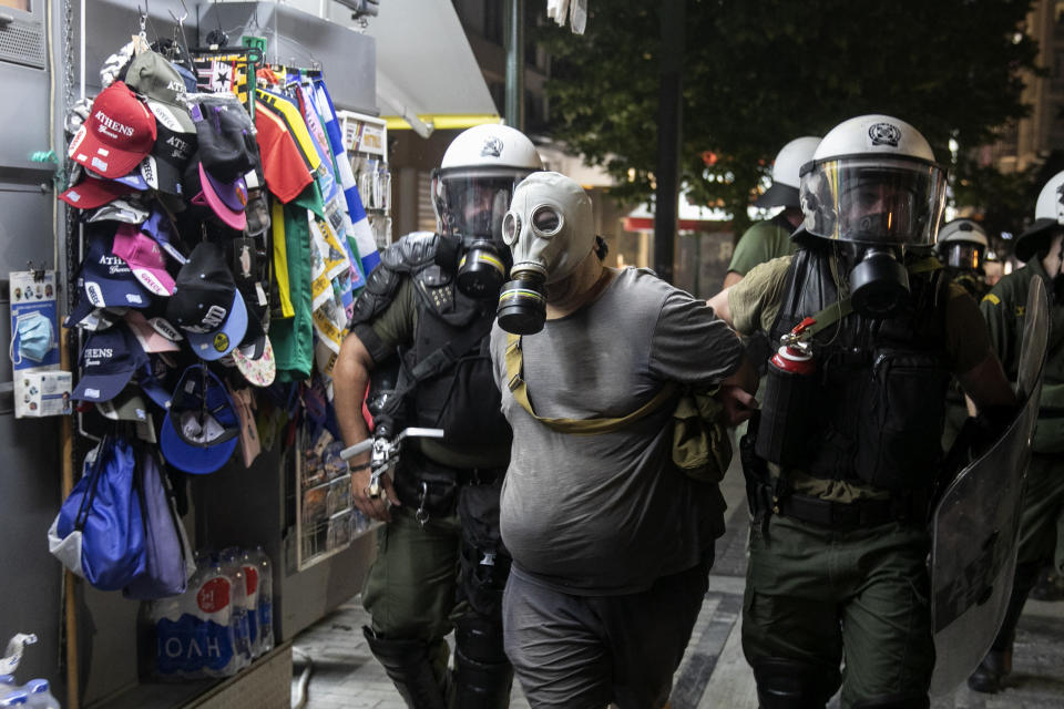 Police detain a masked anti-vaccine protester during clashes around central Syntagma square in Athens, Greece, Sunday, Aug. 29, 2021. Police used tear gas to disperse thousands of protesters opposing government's plans for mandatory vaccination and new testing requirements and attendance restrictions on people who aren't vaccinated against COVID-19. (AP Photo/Yorgos Karahalis)