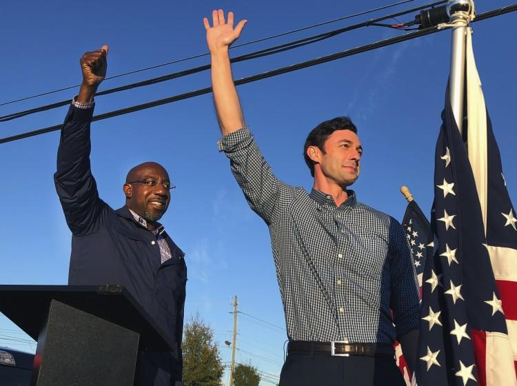 MARIETTA, GA - NOVEMBER 15: Georgia Democratic candidates for U.S. Senate Raphael Warnock, left, and Jon Ossoff, right, gesture toward a crowd during a campaign rally on Sunday, Nov. 15, 2020, in Marietta, Ga.