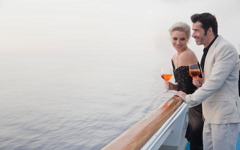 Couple relaxing on deck of cruise - Credit: Getty