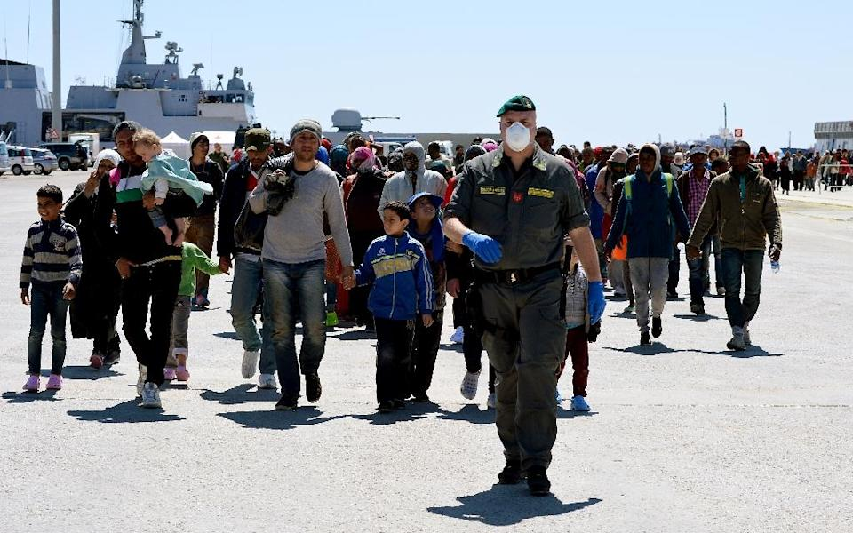 Rescued migrants walk along the quayside after disembarking from the Italian Navy vessel Bettica in the Sicilian harbour of Augusta, on April 22, 2015 (AFP Photo/Alberto Pizzoli)