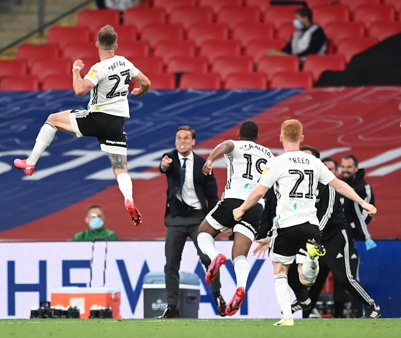 Joe Bryan (top left) and his Fulham teammates and coaches celebrate the journeyman fullback's extra-time game-winning goal that took the club back to the Premier League. (Shaun Botterill/Getty Images)