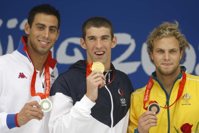 Gold medalist United States' Michael Phelps, center, reacts during the presentation ceremony for the men's 100-meter butterfly final during the swimming competitions in the National Aquatics Center at the Beijing 2008 Olympics in Beijing, Saturday, Aug. 16, 2008. At left is Serbia's Milorad Cavic, who took silver and and at right is bronze medalist Andrew Lauterstein from Australia. (AP Photo/Mark Baker)