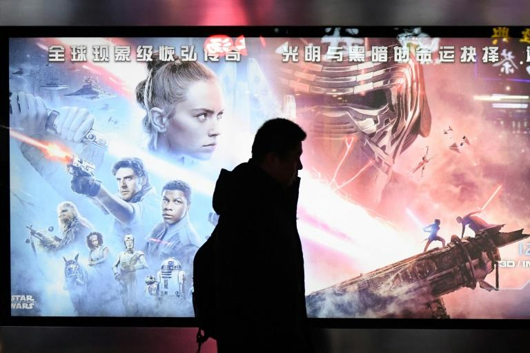 "A man walking past a poster for the latest Star Wars movie, ""The Rise of Skywalker"", in Beijing (AFP Photo/GREG BAKER)"