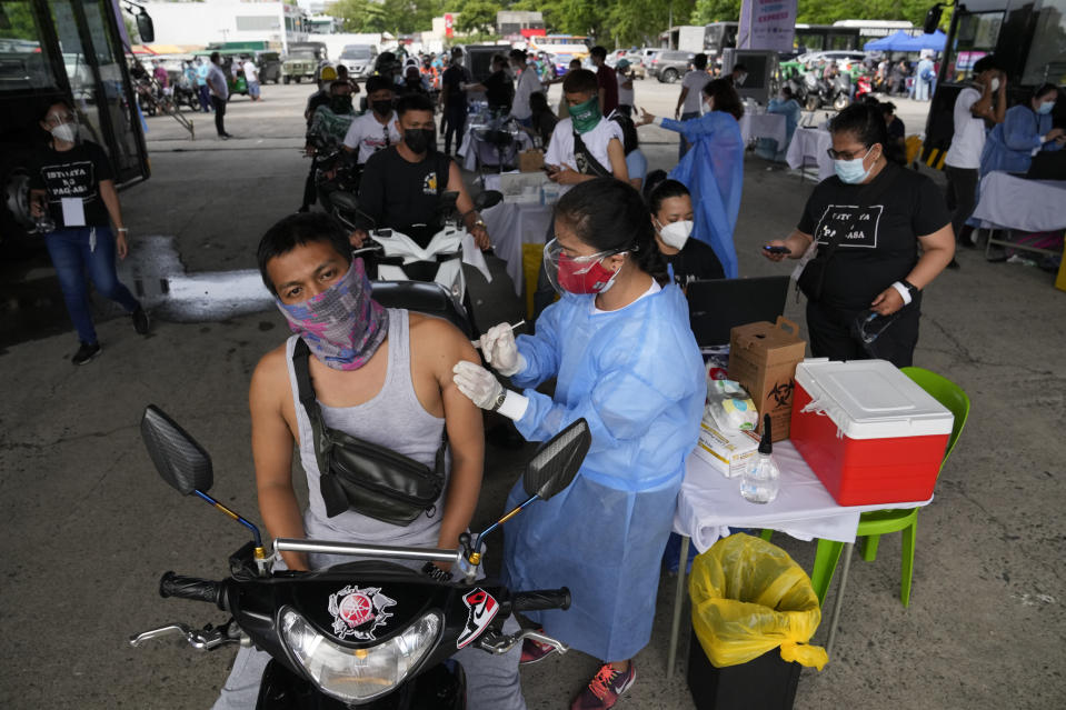 A motorcycle rider is inoculated with China's Sinovac COVID-19 vaccine at a drive-thru vaccination center in Manila, Philippines, Tuesday, June 22, 2021. The Philippine president has threatened to order the arrest of Filipinos who refuse COVID-19 vaccination and told them to leave the country for hard-hit countries like India and the United States if they would not cooperate with massive efforts to end the pandemic. (AP Photo/Aaron Favila)