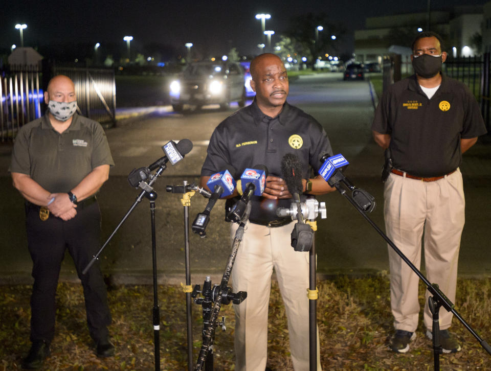 New Orleans Police Chief Shaun Ferguson, center, updates the media on the investigation of a shooting at George Washington Carver High School where a law enforcement officer was fatally shot as a basketball game was being played in New Orleans, Friday, Feb. 26, 2021. (Max Becherer/The Times-Picayune/The New Orleans Advocate via AP)