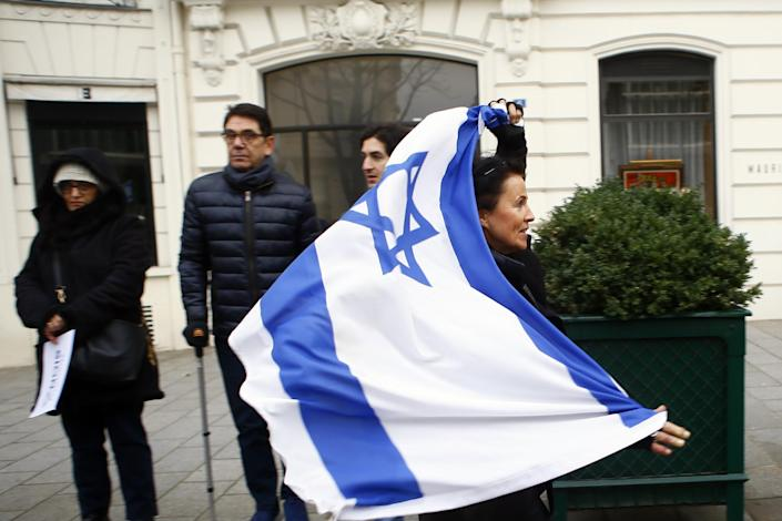 A woman runs with an Isreali flag as pro-Israel demonstrators gather in front of Israel embassy in Paris, France, Sunday, Jan. 15, 2017. Fearing a new eruption of violence in the Middle East, more than 70 world diplomats gathered in Paris on Sunday to push for renewed peace talks that would lead to a Palestinian state. (AP Photo/Francois Mori)