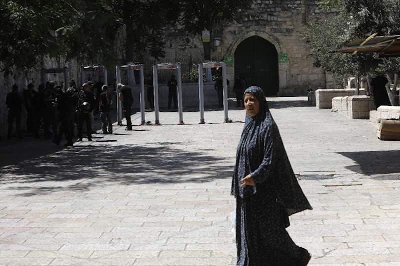 A Palestinian woman walks by as Israeli border policemen install metal detectors outside the Lion's Gate, a main entrance to Al-Aqsa mosque compound, in Jerusalem's Old City, on July 16, 2017