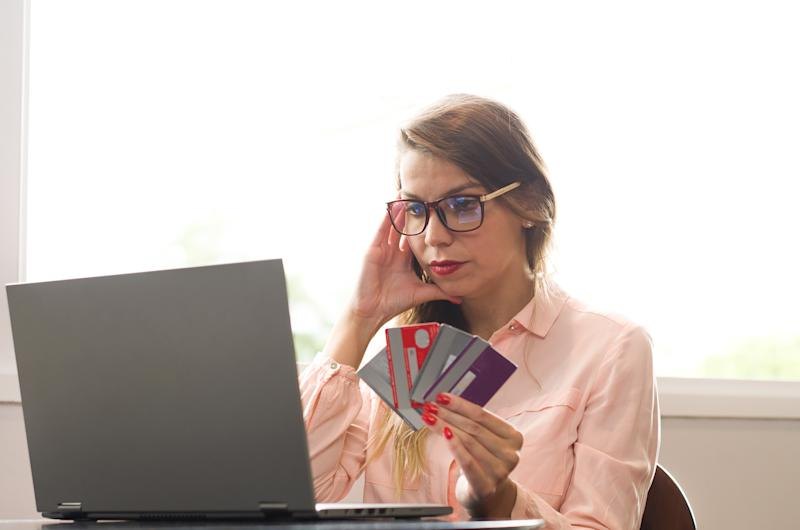 Stressed woman with handful of credit cards looking at laptop.