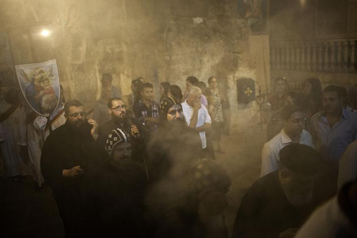 Coptics Priests and Monks purify with incense the holy cave during a procession within Al-Mahraq monastery in Assiut, Upper Egypt, Tuesday, Aug. 6, 2013. Islamists may be on the defensive in Cairo, but in Egypt's deep south they still have much sway and audacity: over the past week, they have stepped up a hate campaign against the area's Christians. Blaming the broader Coptic community for the July 3 coup that removed Islamist President Mohammed Morsi, Islamists have marked Christian homes, stores and churches with crosses and threatening graffiti. (AP Photo/Manu Brabo)