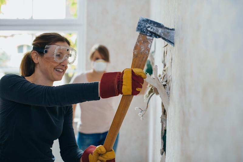 Woman severing old wall in a house with a big axe.