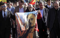 """A man holds a drawing of Spanish dictator Gen. Francisco Franco as they gather outside Mingorrubio's cemetery, outskirts of Madrid, Thursday, Oct. 24, 2019. Spain's interim prime minister, Pedro Sánchez, says the exhumation of Spanish dictator Gen. Francisco Franco """"puts an end to a moral affront that is the exaltation of dictator in a public place."""" Earlier, Franco's remains were taken from his grandiose Valley of the Fallen mausoleum outside Madrid to their new resting place at the Mingorrubio cemetery, 57 kilometers (35 miles) away. (AP Photo/Manu Fernandez)"""