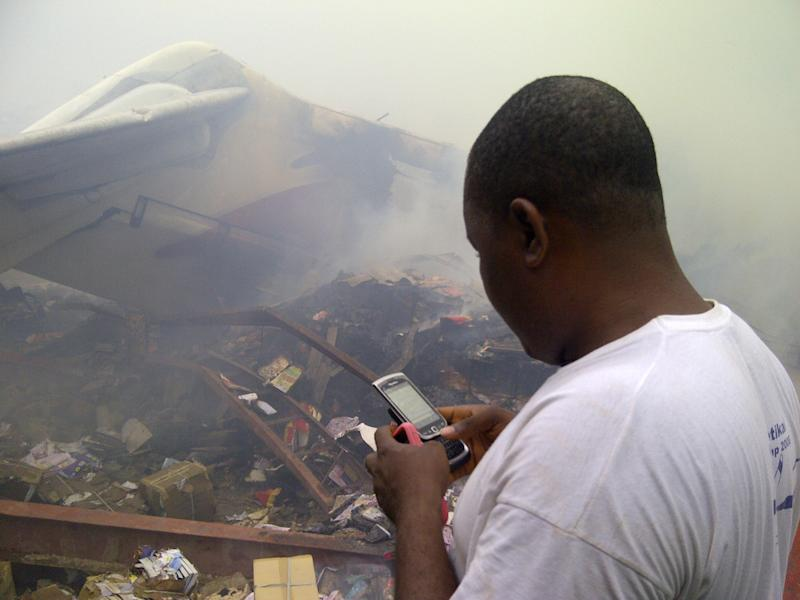 A man using his cell phone stands near the wreckage of a crashed passenger plane in a neighborhood just north of Murtala Muhammed International Airport, in Lagos, Nigeria, Sunday, June 3, 2012. The passenger plane carrying more than 150 people crashed in Nigeria's largest city on Sunday, government officials said. The Lagos state government said in a statement that 153 people were on the Dana Air flight Sunday.(AP Photo/Jon Gambrell)