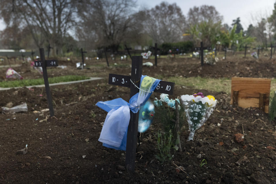 A national flag is wrapped around a cross on a gravesite in the COVID-19 section of the Chacarita cemetery in Buenos Aires, Argentina, Tuesday, July 13, 2021. Recent coronavirus variants have helped spread the disease even faster and the vaccine program, while making progress, is still falling short. (AP Photo/Victor R. Caivano)