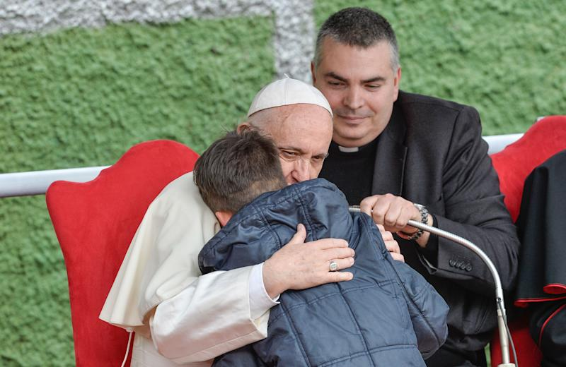 Pope Francis hugs a child named Emanuele at the St. Paul of the Cross parish during a pastoral visit on April 15, 2018.