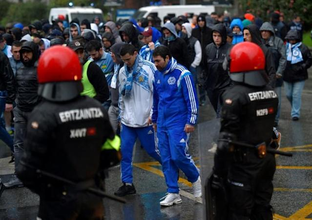 High tension: Marseille fans walk past Basque autonomous police officers outside the San Mames stadium before the Europa League match against Athletic Bilbao