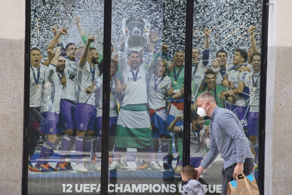A man and a young boy walk past a Real Madrid poster of the team celebrating in a merchandising shop in Madrid, Spain, Monday, April 19, 2021. UEFA president Aleksander Ceferin says players at the 12 clubs setting up their own Super League could be banned from this year's European Championship and next year's World Cup. Ceferin spoke after a UEFA executive committee meeting held only hours of the English, Italian and Spanish clubs announced the project that threatens to split European soccer. (AP Photo/Paul White)