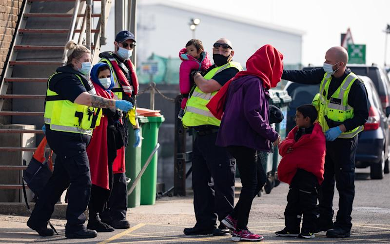 A migrant family is taken into port after being intercepted by Border Force officials in the English Channel - Getty