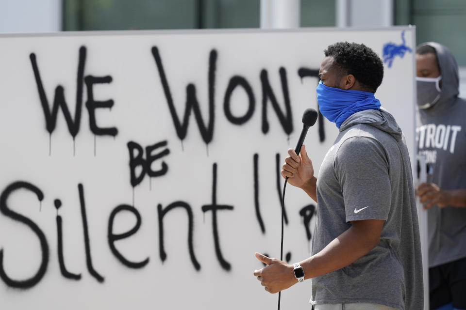 """Trey Flowers, wearing a face covering, speaks into a microphone in front of a whiteboard that reads, """"We won't be silent!"""""""