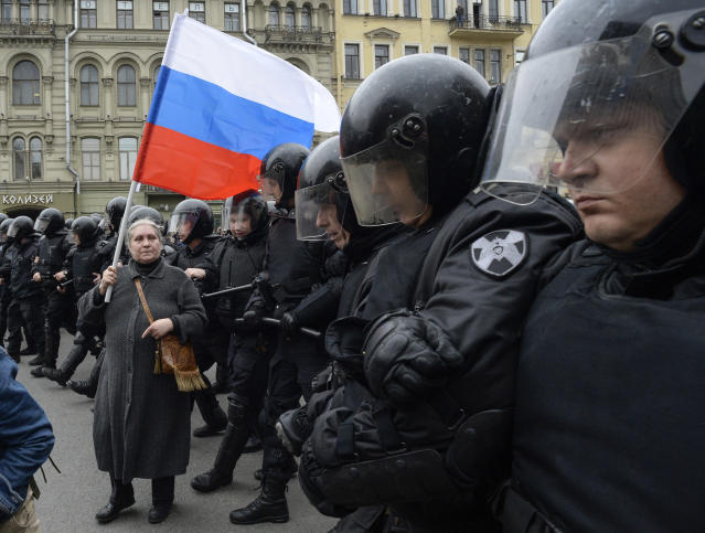 <p>A woman holding a Russian flag stands in front of riot police blocking an area during an unauthorized anti-Putin rally called by opposition leader Alexei Navalny on May 5, 2018 in Saint Petersburg, two days ahead of Vladimir Putin's inauguration for a fourth Kremlin term. (Photo: Olga Maltseva/AFP/Getty Images) </p>