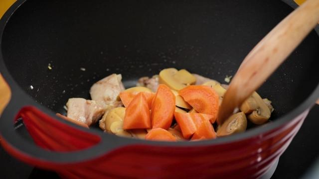 stir frying carrots, mushrooms and chicken in a pot