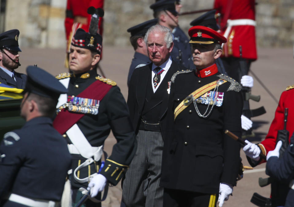 Prince Charles, centre, walks in the procession to St George's Chapel, Windsor Castle, Windsor, England, Saturday April 17, 2021, during the funeral of Britain's Prince Philip. Prince Philip died April 9 at the age of 99 after 73 years of marriage to Britain's Queen Elizabeth II. (Steve Parsons/Pool via AP)