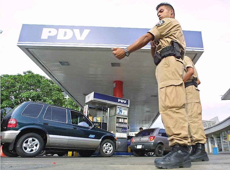 A policeman directs cars at a PDVSA gas station in Caracas (AFP Photo/JUAN BARRETO)