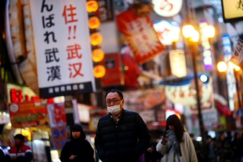A man, wearing protective mask following an outbreak of the coronavirus disease (COVID-19), walks on an almost empty street in the Dotonbori entertainment district of Osaka