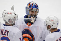 New York Islanders goaltender Ilya Sorokin (30) celebrates with Josh Bailey, left, and Cal Clutterbuck after Bailey's winning overtime goal in Game 5 of an NHL hockey Stanley Cup first-round playoff series against the Pittsburgh Penguins in Pittsburgh, Monday, May 24, 2021. (AP Photo/Gene J. Puskar)