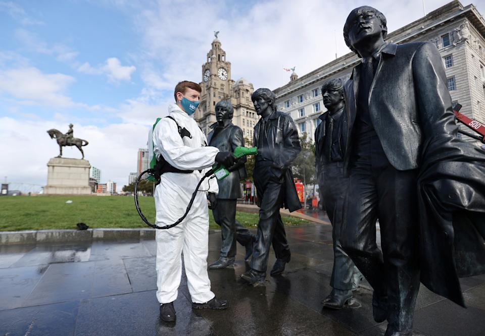A man disinfects a statue of the Beatles amid the outbreak of the coronavirus disease (COVID-19), in Liverpool, Britain October 1, 2020. REUTERS/Carl Recine REFILE - CORRECTING CITY IN HEADLINE