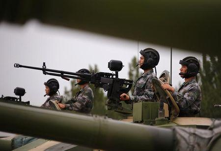 Soldiers of People's Liberation Army (PLA) stand inside tanks at a drill during an organised media tour at a PLA engineering academy in Beijing