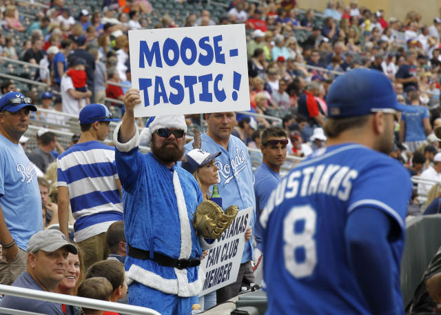 A Kansas City Royals fan cheers Kansas City Royals third baseman Mike Moustakas (8) as he takes the field before a baseball game against the Minnesota Twins in Minneapolis, Sunday, Aug. 17, 2014. (AP Photo/Ann Heisenfelt)