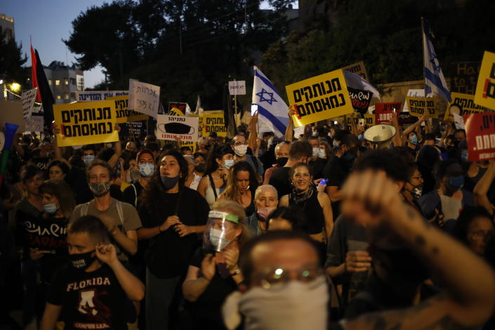 Demonstrators, defying orders to maintain social distancing requirements, chant slogans and blow horns outside the Prime Minister's residence in Jerusalem, Tuesday, July 14, 2020. Thousands of Israelis demonstrated outside the official residence of Benjamin Netanyahu, calling on the embattled Israeli leader to resign as he faces a trial on corruption charges and grapples with a deepening coronavirus crisis. (AP Photo/Ariel Schalit)