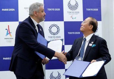 Etienne Thobois, Paris 2024 Director General, shakes hands with Toshiro Muto, Tokyo 2020 CEO, after signing documents during a ceremony marking conclusion of MoU between Tokyo 2020 and Paris 2024 Olympic Games in Tokyo, Japan, July 11, 2018. REUTERS/Kim Kyung-Hoon
