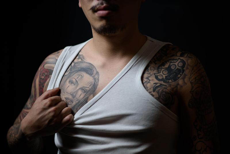 Tattoo artist Horisen, 28, shows off his tattoos at the Tattooism studio in Seoul on December 9, 2014 (AFP Photo/Ed Jones)